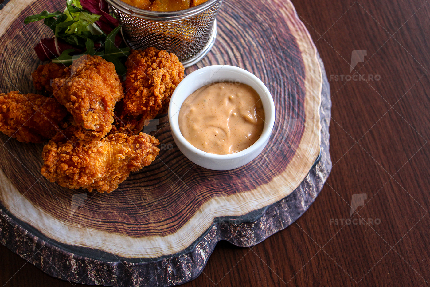 Spicy chicken strips on wooden plate with sauce over, top view, closeup